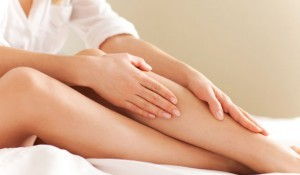 woman-applying-lotion-to-her-leg-300x175